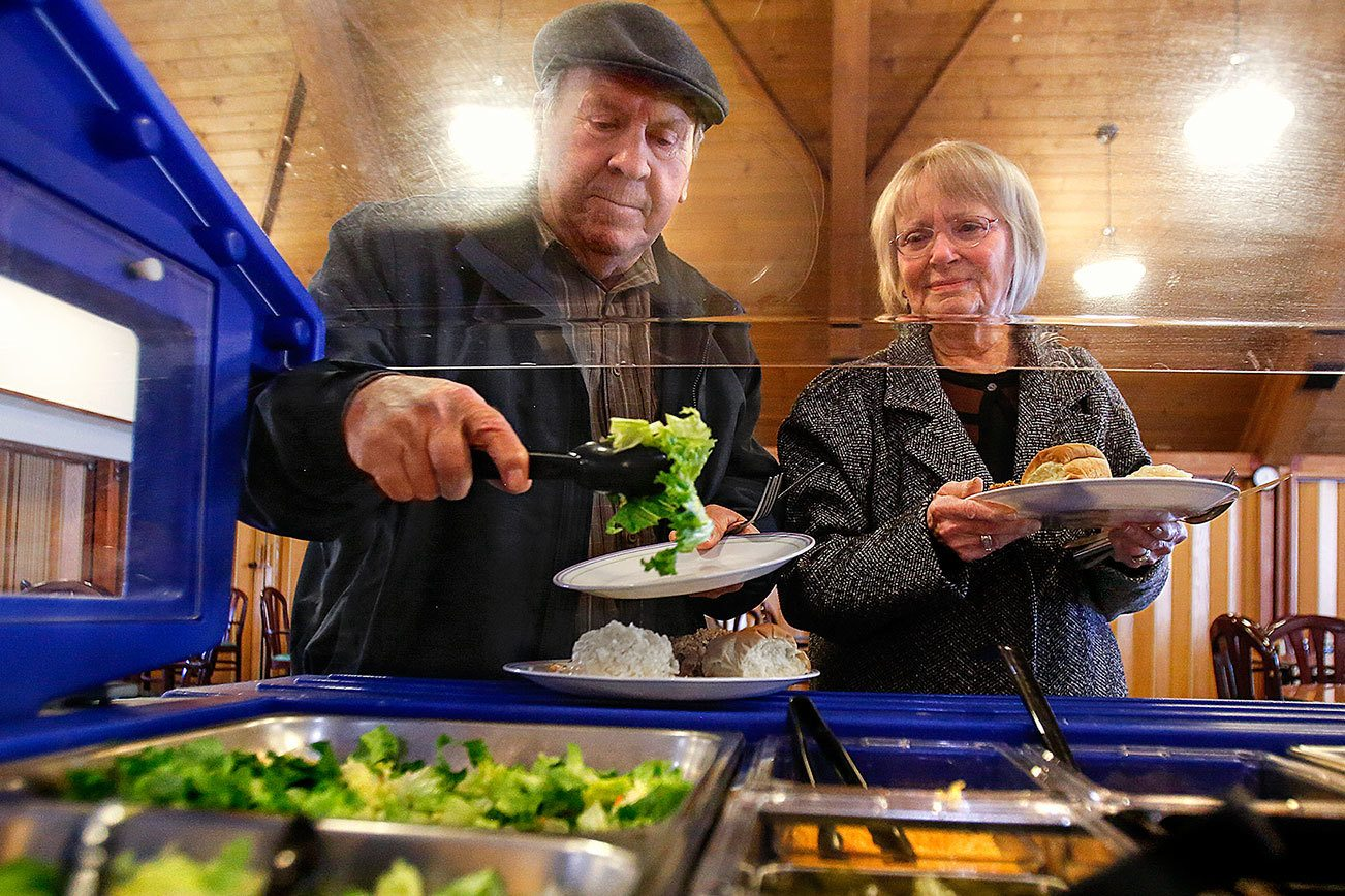 Frank and Nancy Roesler, of Startup, grab a little salad with lunch Jan. 3, two days before their 66th wedding anniversary, at the Sky Valley Senior Center in Sultan. The center, started by a group of seniors with help from Volunteers of America to offer meals, exercise classes and more, has been struggling to keep the lights on, despite a fundraising campaign launched by the VOA. (Dan Bates / The Herald)