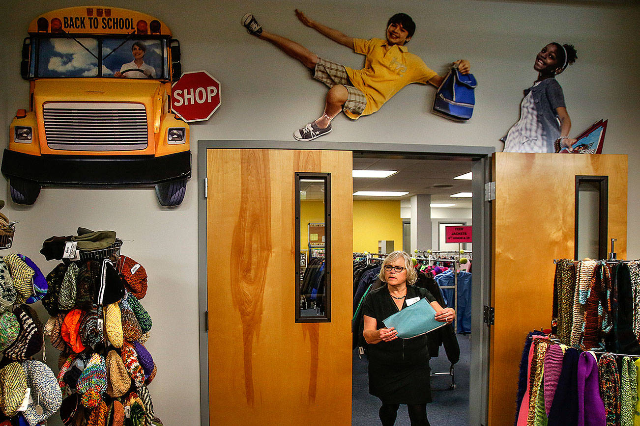 Providing more than the expected: Diane Pedack works with the childrens' clothes inventory at Operation School Bell, which includes a wonderful selection of fine hand-knitted hats and scarfs. (Dan Bates / The Herald)